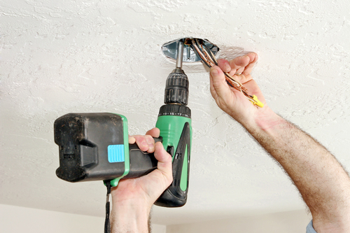 security system maintenance, hand with drill