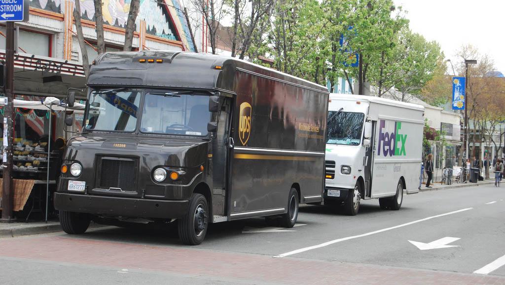 UPS - FedEx trucks delivering packages, packages